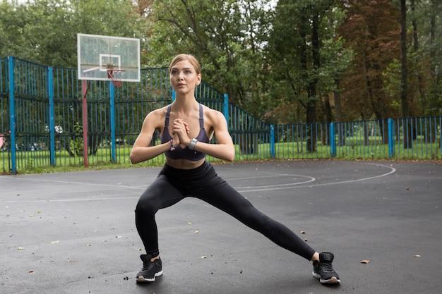Фитнес-модель в спортивном топе и леггинсах делает спортивные упражнения на спортивных площадках в парке