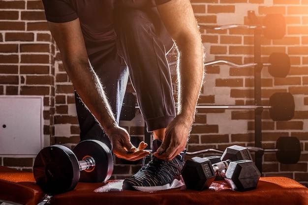 피트니스 동기 부여 및 근육 훈련 개념. 햇빛에 구두 끈을 묶는 운동화에있는 남자.