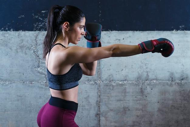 Мускулистая женщина фитнеса с боксерскими перчатками, тренирующаяся в тренажерном зале