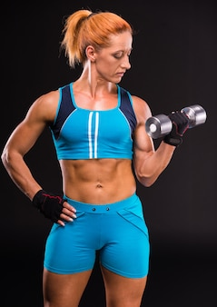 Fitness, muscular woman with barbells