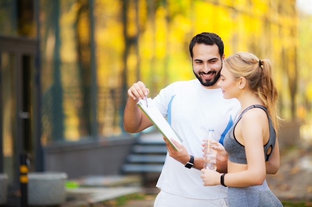Fitness. personal trainer takes notes while woman exercising outdoor.
