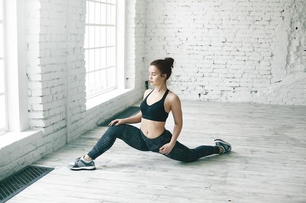 フィットネス、運動、アクティブで健康的なライフスタイルのコンセプト。あなたの情報のためのコピースペースのある大きなホールでフロントスプリットをしている完璧なアスリートボディを持つ魅力的な若い女性の写真