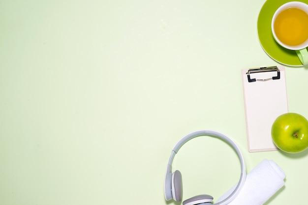 フィットネスプランのコンセプト。オープンノートブックとパステルカラーの背景にヘッドフォン、お茶、リンゴ、ヘッドフォン。