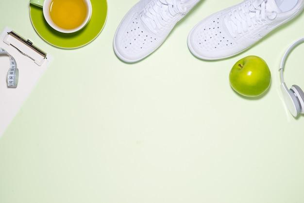 피트니스 계획 개념입니다. 열린 노트북이 있는 파스텔 색상 배경에 운동화, 차, 사과, 헤드폰.