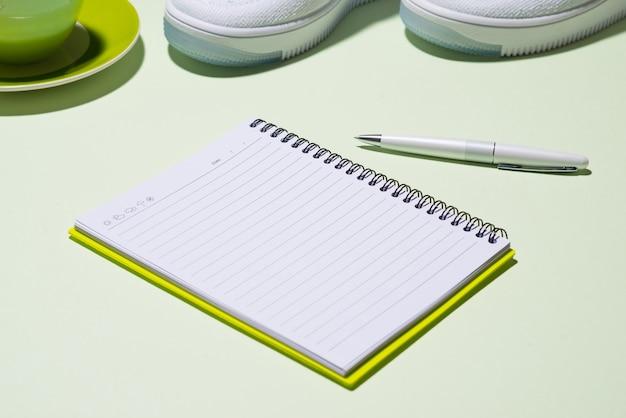 フィットネスプランのコンセプト。オープンノートブックとパステルカラーの背景にスニーカー、お茶、リンゴ、ヘッドフォン。