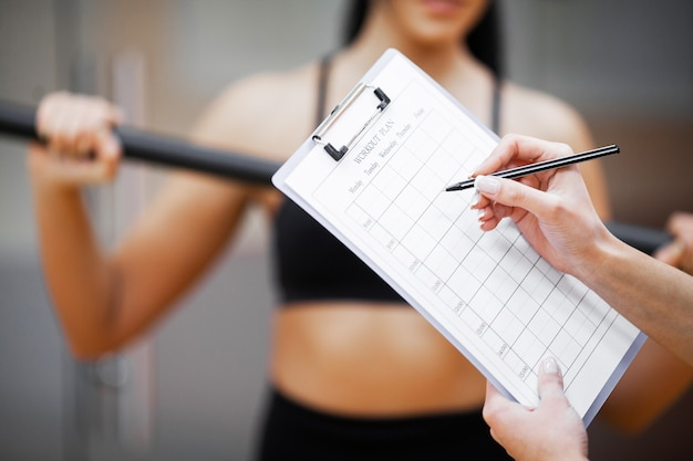 Fitness plan, sports trainer amounts to workout plan close-up