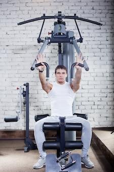Фитнес - мощный мускулистый мужчина делает тяжелую атлетику в тренажерном зале