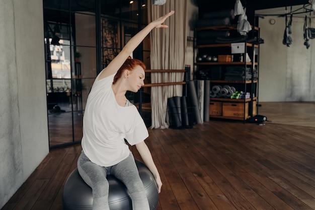 피트니스 연습. 큰 은색 운동복에 앉아 스포츠 클럽이나 스튜디오에서 운동하고 한 손을 들어 스트레칭 운동을 하는 운동복을 입은 젊은 활동적인 빨간 머리 여성