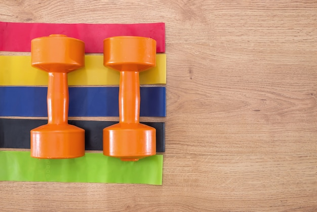 Фитнес-резинки и гантели на деревянной поверхности.