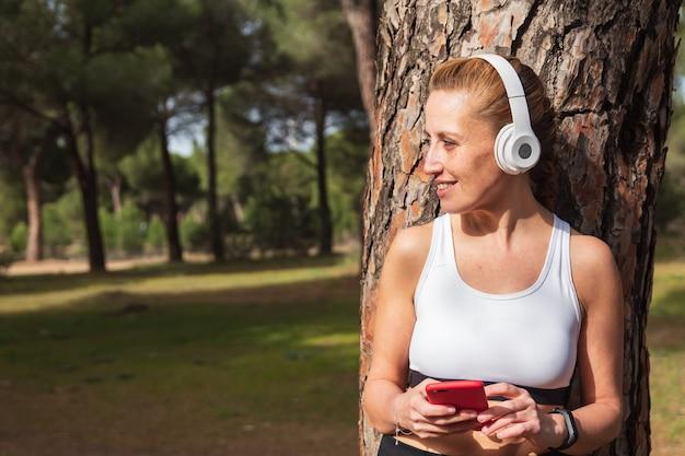 스마트 시계 전화에 헤드폰으로 음악을 듣고 피트니스 러너 소녀. 스포츠, 기술, 활동적인 라이프스타일 개념 및 복사 공간.