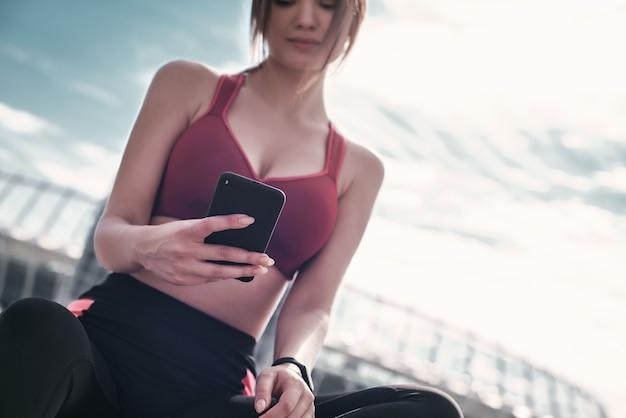 携帯スマートフォンアプリのフィットネスランナーがイヤホンで音楽を聴いて進行状況を追跡する