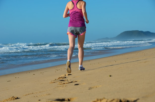 Fitness and running on beach, woman runner legs in shoes on sand near sea, healthy lifestyle and sport concept