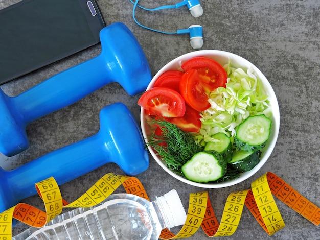 Фитнес-салат, гантели и рулетка