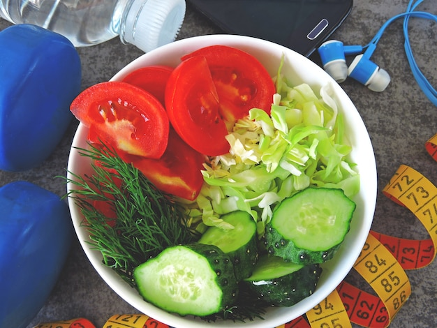 Fitness salad, dumbbells and measuring tape