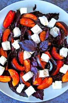 Fitness salad with plums, feta and basil. delicious and nutritious salad with plums and white cheese