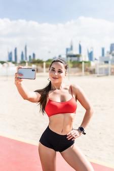 トレーニング後のフィットネスselfie女性のセルフポートレート。スポーツアスリートは、ビーチでランニングやトレーニングを屋外でした後、電話でselfies写真を撮ります。幸せな笑顔の女性スポーツモデルに合います。
