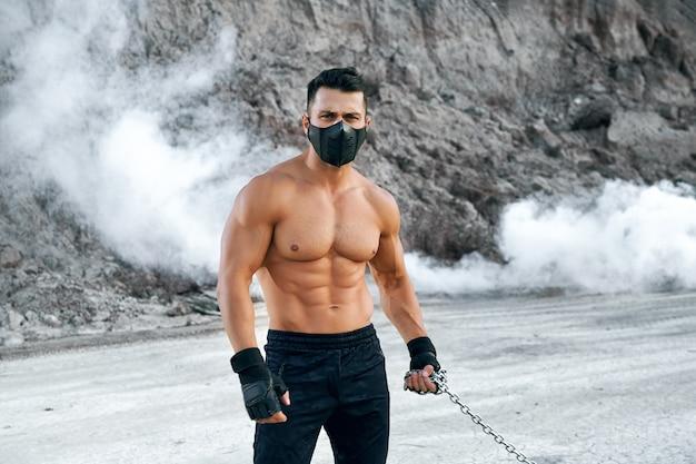 砂場の間に立っている間、手に金属チェーンを保持しているフィットネス上半身裸の男。新鮮な空気でスポーツ活動をしている黒い医療マスクのアクティブな男。
