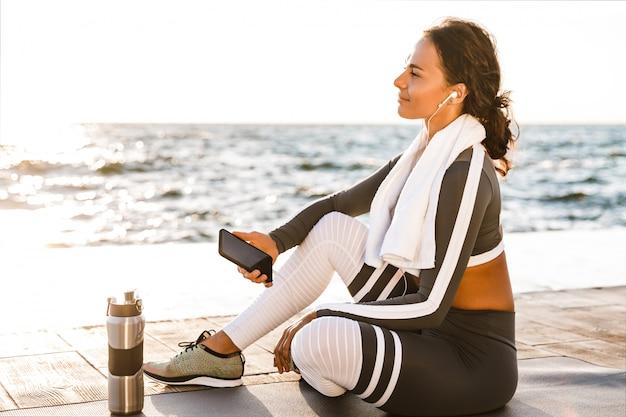 Женщина фитнеса усмехаясь смотря в сторону слушая музыка с наушниками