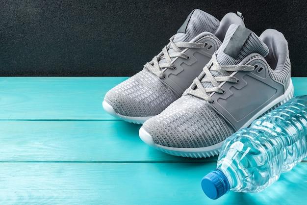 青い木製の背景にフィットネススニーカーと水のボトル。