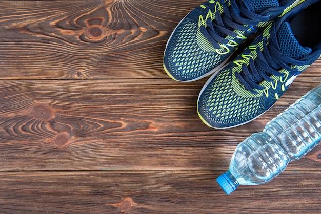 Кроссовки фитнеса и бутылка воды на деревянных фоне.
