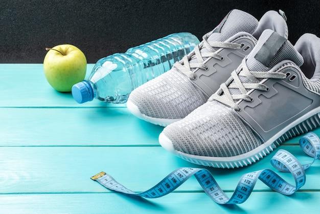 Кроссовки фитнеса, зеленое яблоко, рулетка и бутылка воды на синем деревянном фоне.