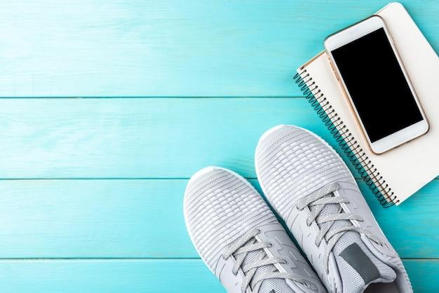 Фитнес-кроссовки, ноутбук, мобильный телефон и фитнес-браслет на синем деревянном фоне.