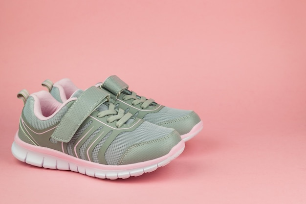 Fitness sneakers on pastel pink background. sports shoes. color trend.