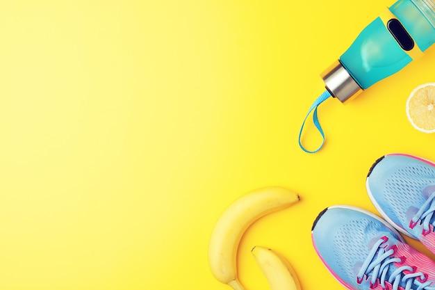 黄色の背景に果物とフィットネススニッカーズ