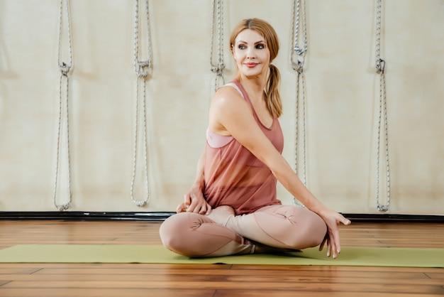 Концепция фитнеса, спорта и здорового образа жизни - женщина делает упражнения йоги в студии