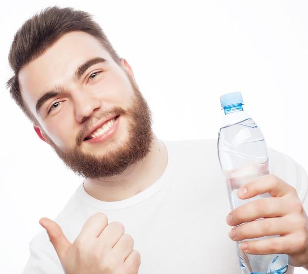 피트 니스, 스포츠 및 라이프 스타일 개념: 물 한 병과 흰색 셔츠를 입고 웃는 근육 질의 낚시를 좋아하는 남자. 화이트에 격리.
