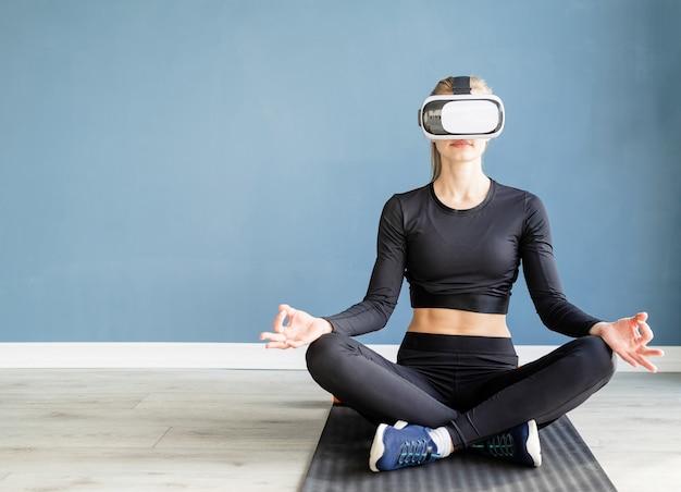 피트니스, 스포츠 및 기술. 피트니스 매트에 요가 하 고 가상 현실 안경을 쓰고 젊은 운동 여자
