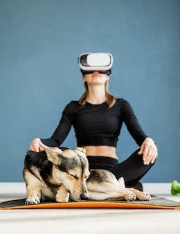 フィットネス、スポーツ、テクノロジー。犬と一緒にフィットネスマットの上に座ってバーチャルリアリティ眼鏡をかけている若い運動女性