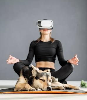 피트니스, 스포츠 및 기술. 강아지와 함께 피트니스 매트에 앉아 가상 현실 안경을 쓰고 젊은 운동 여자