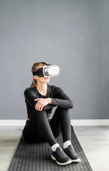 피트니스, 스포츠 및 기술. 피트니스 매트에 앉아 가상 현실 안경을 쓰고 젊은 체육 여자