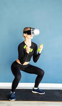 피트니스, 스포츠 및 기술. 파란색 배경에서 아령으로 쪼그리고 가상 현실 안경을 쓰고 젊은 체육 여자