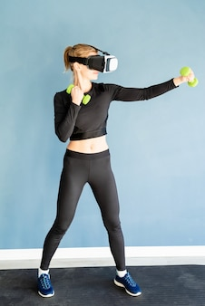 피트니스, 스포츠 및 기술. dubbells와 함께 운동 피트니스 매트에 서 가상 현실 안경을 착용하는 젊은 운동 여자