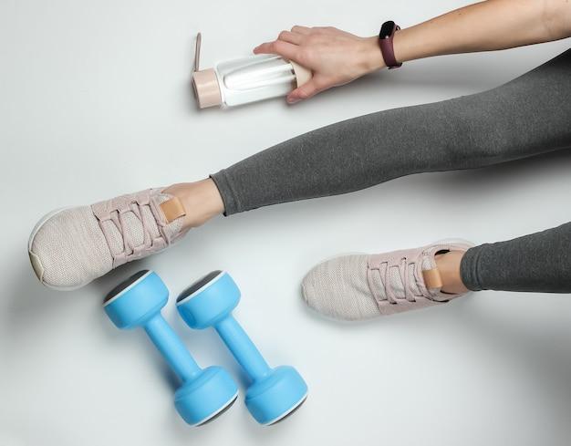 Фитнес, спортивная концепция. женские ножки, одетые в леггинсы и кроссовки, сидят на белом фоне с бутылкой воды для тренировки и гантелями. вид сверху