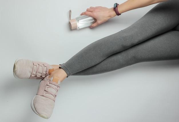 Фитнес, спортивная концепция. женские ножки, одетые в леггинсы и кроссовки, сидят на белом фоне с бутылкой воды для тренировки. вид сверху