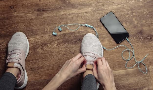 피트니스, 스포츠 개념. 스마트 폰과 이어폰으로 바닥에 앉아있는 동안 달리기위한 스포츠 신발 끈을 묶는 여자.