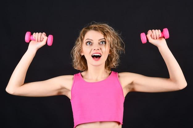 フィットネススポーツコンセプトワークアウトブロンドの女の子はピンクのダンベルを保持しますフィットネスの女の子の健康的なライフスタイル