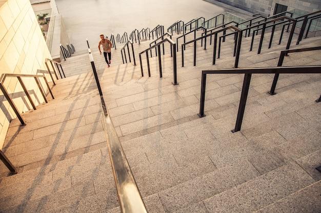 Фитнес, спорт, упражнения и концепция здорового образа жизни людей. человек бегает по лестнице в городе.