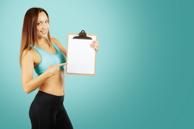 Fitness, sport, exercising and diet concept - smiling young woman personal trainer with clipboard