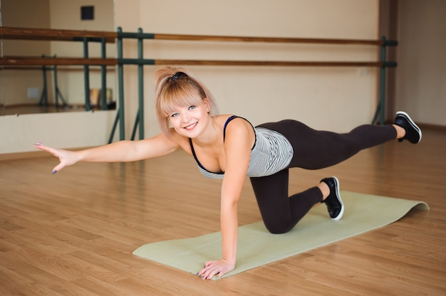 Fitness, sport, exercising lifestyle - happy women wear in bodysuits doing exercises at gym.