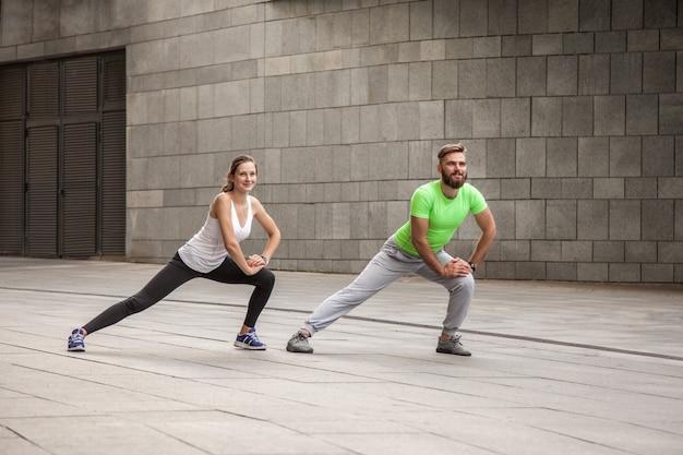 フィットネス、スポーツ、エクササイズ、トレーニング、そして人々のコンセプト-街の通りのベンチで上腕三頭筋のディップエクササイズをしているカップル。