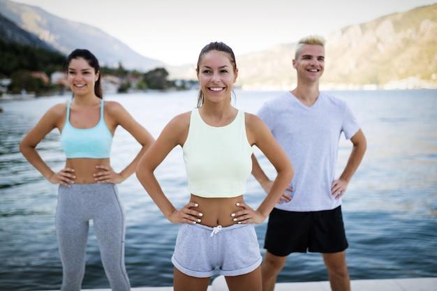 피트니스, 스포츠, 우정, 건강한 생활 방식 개념. 야외에서 운동하고 스트레칭하는 행복한 친구나 스포츠맨