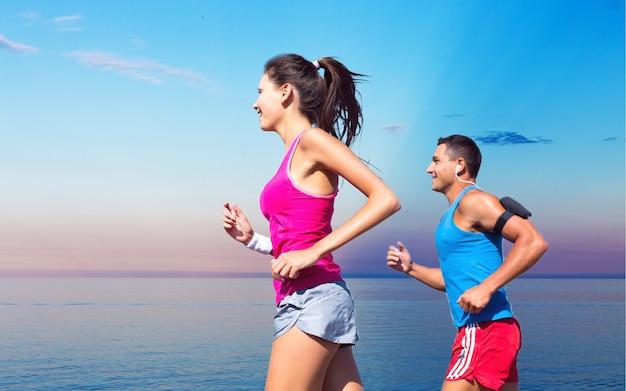 Концепция фитнеса, спорта, дружбы и образа жизни - улыбающаяся пара работает вместе