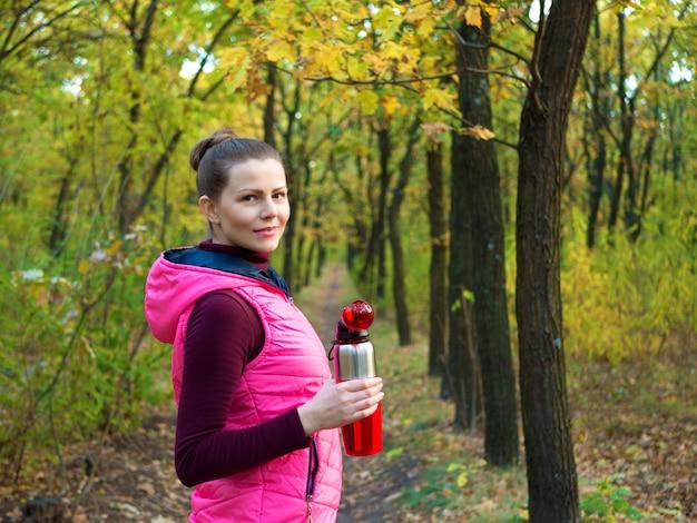 가 공원에서 피트 니스 스포츠 소녀는 스포츠 병에서 물 또는 등장 음료를 마신다.