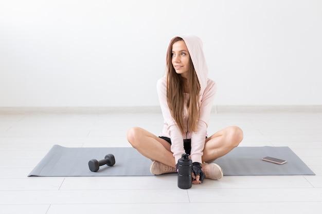 フィットネス、スポーツ、人々の概念-若い女性は、運動後にマットに座って横向きになり、リラックスしています。
