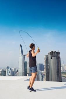 Фитнес, спорт, люди, упражнения и концепция образа жизни - человек прыгает со скакалкой на открытом воздухе