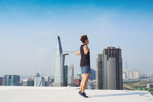 피트니스, 스포츠, 사람, 운동 및 라이프스타일 개념 - 야외에서 줄넘기로 건너뛰는 남자